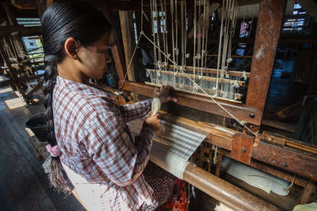 handloom: The local worker is weaving with handloom in the factory center of famous lake on December 26, 2013 in Inle, Myanmar.