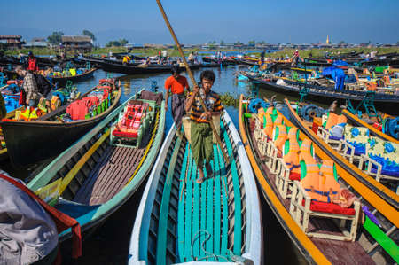 The local market are crowding with row boats of tourists and local people in the center of famous lake on December 26, 2013 in Inle, Myanmar. Editorial