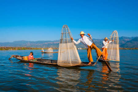 The local fishermen are fishing by boat in unique style. By using their feet to control the boat on famous lake on December 25, 2013 in Inle, Myanmar.