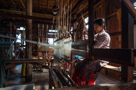 The local worker is weaving with handloom in the factory center of famous lake on December 26, 2013 in Inle, Myanmar.