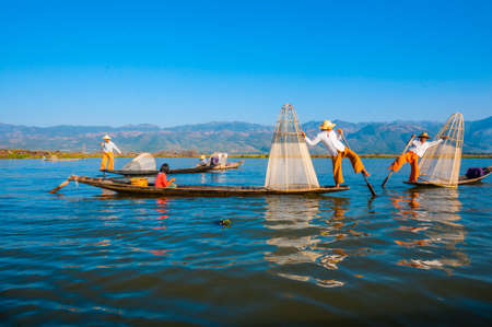 december 25: The local fishermen are fishing by boat in unique style. By using their feet to control the boat on famous lake on December 25, 2013 in Inle, Myanmar.