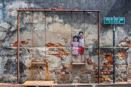 georgetown: Georgetown, Penang, Malaysia - February 19, 2015: Children on the Swing street art on wall by local artist Louis Gan