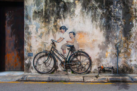 asian art: Georgetown, Penang, Malaysia - February 19, 2015: Little Children on a Bicycle street art on wall by Lithuanian artist Ernest Zacharevic Editorial