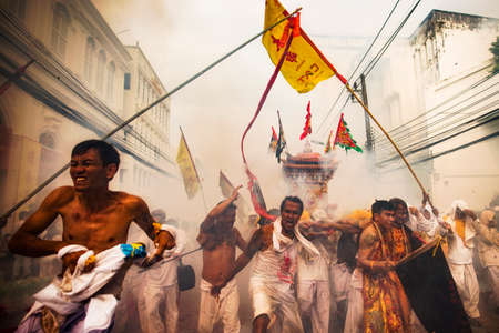 palanquin: Phuket, Thailand - October 18, 2015: Parade of devotees along old town street of Phuket town in vegetarian festival. Editorial