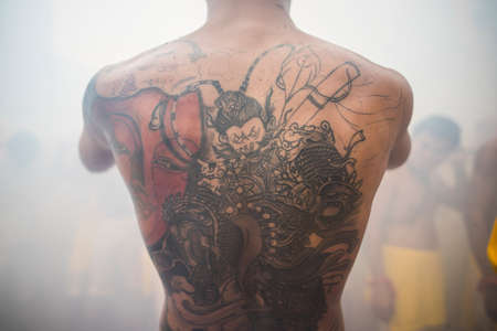 tattoo traditional: Phuket, Thailand - October 18, 2015: Art of body tattoo on the back of young fellow, in the vegetarian festival.