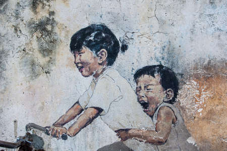 """Georgetown, Penang, Malaysia - February 18, 2015: """"Little Children on a Bicycle"""" street art on wall by Lithuanian artist Ernest Zacharevic in George Town, Penang, Malaysia. Editorial"""