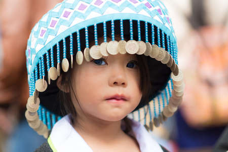 A little girl of local mountaineer tribe Hmong is dressing with traditional costume in Luang Prabang, Laos.