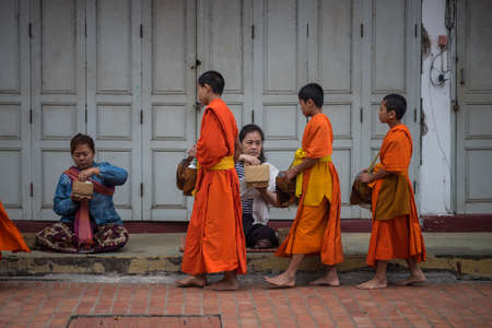 Novice monks are walking to collect alms and offerings in the world heritage site, Luang Prabang, Laos