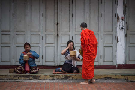 A monk is walking to collect alms and offerings in the world heritage site, Luang Prabang, Laos.