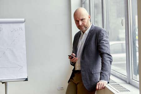 ハゲのビジネスマンが彼の手で携帯電話の側に立って 写真素材