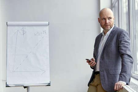 両手で携帯と立っているハゲの実業家