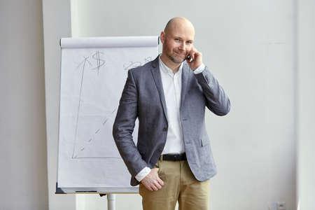 電話通話中に笑みを浮かべてハゲの実業家