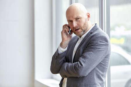 携帯電話を押しウィンドウに戻って立っている男