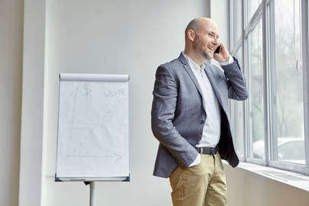 窓の近くの電話に笑顔の実業家