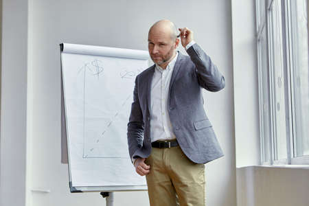 Bald Businessman Scratching his Head With a Marker