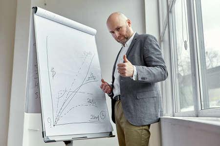 ボード上のグラフの近くに立って悲しいハゲ実業家
