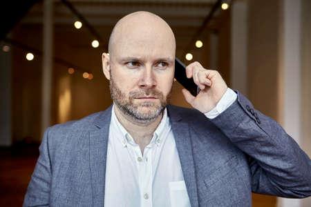 電話をかけるハゲの実業家