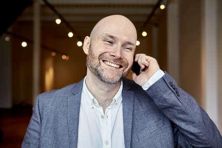 電話通話中に笑っているハゲの実業家