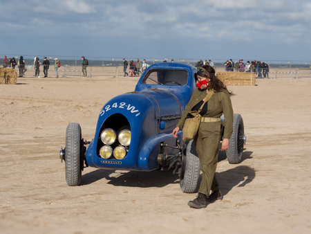 woman in a masthead and retro jumpsuit next to an old Renault car model on a beach in Normandy, France. Normandy Race Beach