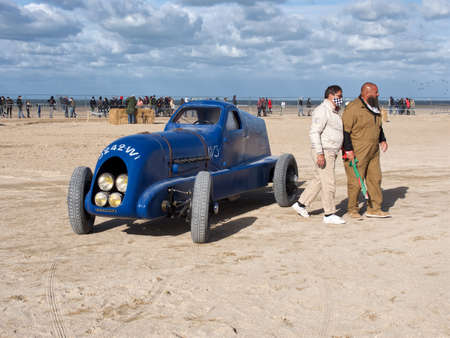 driver in a white suit and a man in a dark suit with a flag in the mask next to an old Renault car model on a beach in Normandy, France. Normandy Race Beach