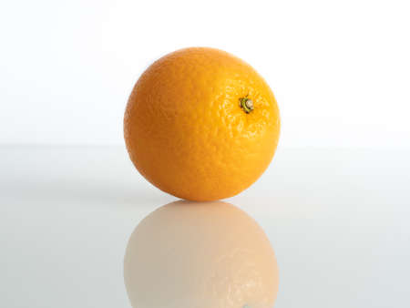 an orange inch on a white background in reflection of the base Stockfoto