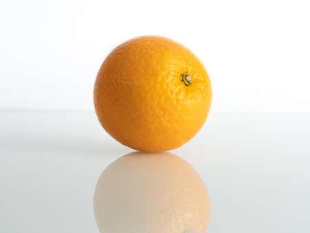 an orange inch on a white background in reflection of the base Reklamní fotografie