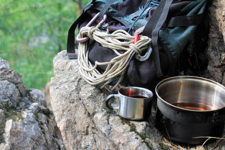 forest tea: Backpack, pot and mug of tea on the cliff top above the green forest