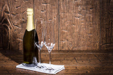 wine glasses: Bottle of champagne and two empty wine glasses are standing on a white napkin on an old  table