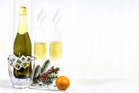copa de vino: Botella de champ�n en cubo de hielo y dos vasos con el mandar�n y la rama de abeto est�n de pie sobre una servilleta