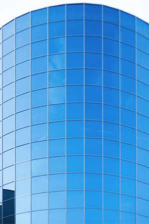 Blue sky in windows of modern office building photo