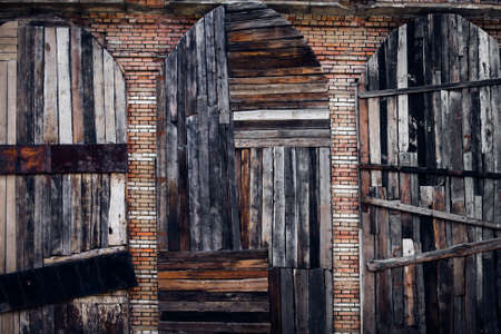 three vintage doors from the old boards on a brick wall background photo