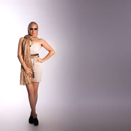 beautiful fashion woman in sunglasses over grey background photo