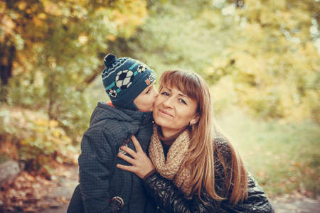 Picture of Son kiss his mother in the autumn forest photo