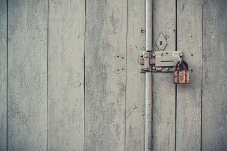 Closeup vintage old wooden door in grungy style with padlock photo