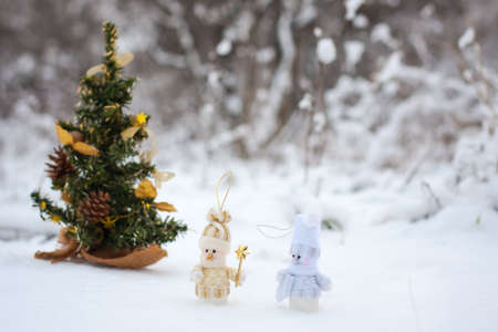 couple of snowmen in the winter woods near a Christmas tree photo