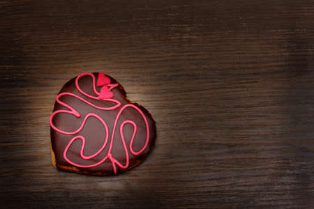 heart shaped cookie on a wooden background photo