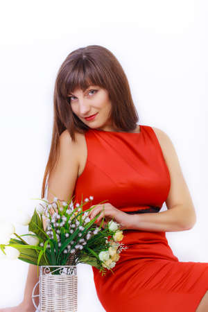 Portrait of a Beautiful girl in a red dress whith spring bouquet on a white background photo