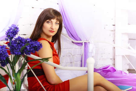 erotically: Girl in red dress reading a book in bed Stock Photo
