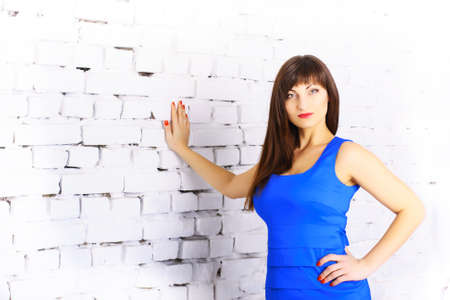 Portrait. Beautiful girl in a blue dress on a background of a white brick wall photo