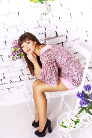 Beautiful Girl with Spring Flowers sitting on the chair. Fresh skin in studio photo