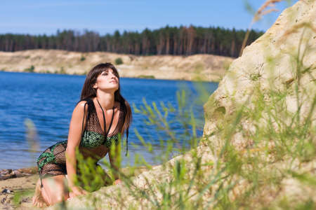 beautiful girl in a swimsuit sitting on sand beach on a background of blue sky photo