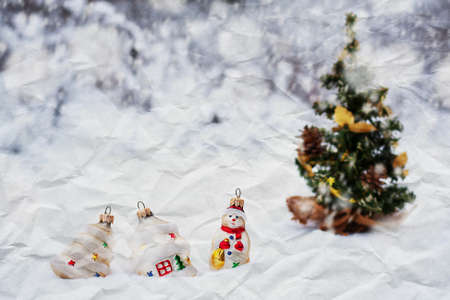 crumpled paper texture. some Christmas toys in the snow near a Christmas tree photo