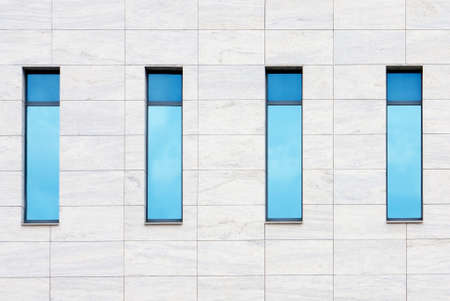 Clouds reflected in windows of modern office building photo
