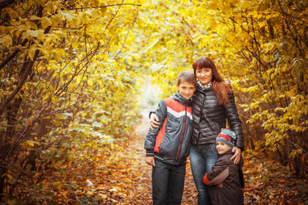 Mother and suns walking in the autumn park. photo