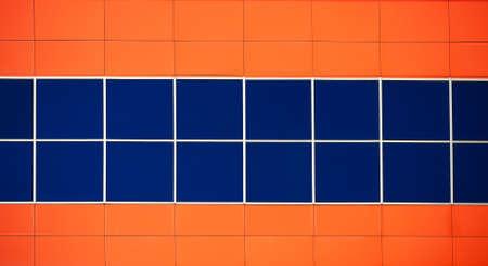 Dark blue windows of modern office building in a orange color. Modern background photo