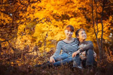 Beautiful mother with son in autumn park Nature photo scene photo
