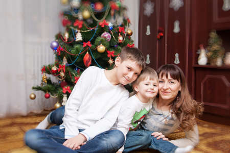 Happy mother and two her children playing near an decorated fir-tree for Christmas photo