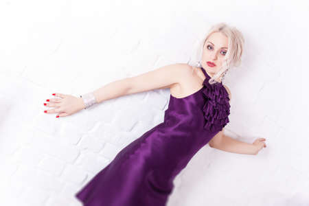 Portrait. Beautiful girl in a purple dress on a background of a white brick wall photo