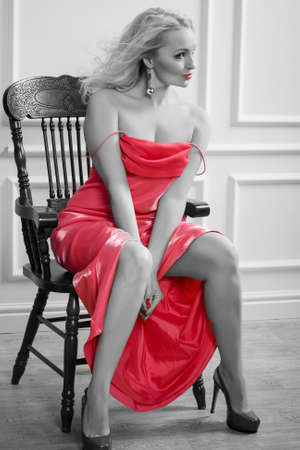 chear: Black white and red color photo of the sexy sensual blonde woman in red dress with long hair sitting on the chear