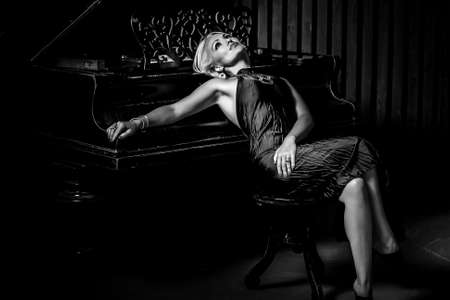 sexy blonde woman sitting near piano. Black and White Fashion studio portrait Stock Photo